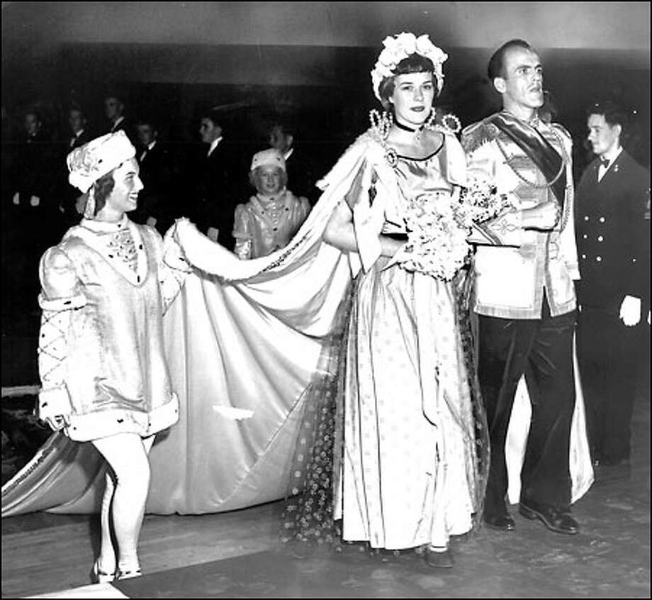 First Seafair queen, 1950: Carrying flowers at her coronation in Seattle's Civic Auditorium, Barbara Curtis, Seafair Queen of the Seas, mounts the stage to meet King Neptune the First. Escorting her at right is the royal chamberlain, Robert Johnson. The first Seafair parade that year drew 150,000 people. Photo: Seattle Post-Intelligencer