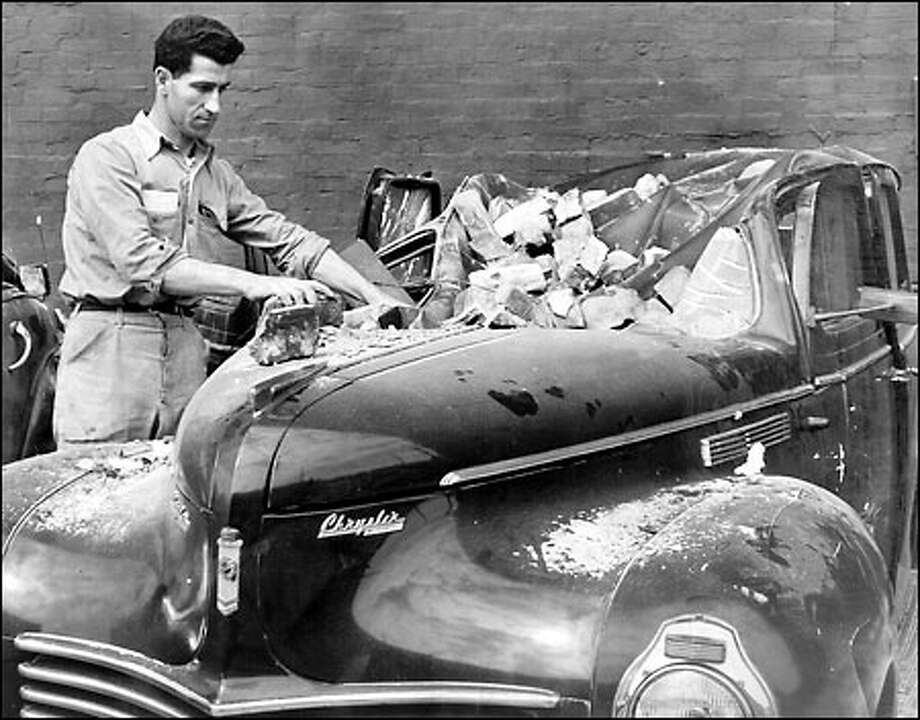 Deadly earthquake, 1949: Nicholas Pillar inspects his automobile at the National Biscuit Co. at 1205 Sixth Ave. S. in Seattle after it was smashed by bricks shaken loose from the building by an earthquake on April 13, 1949. The quake, measuring 7.1 at its epicenter near Olympia, caused seven deaths in the region and inflicted major damage. Photo: Seattle Post-Intelligencer