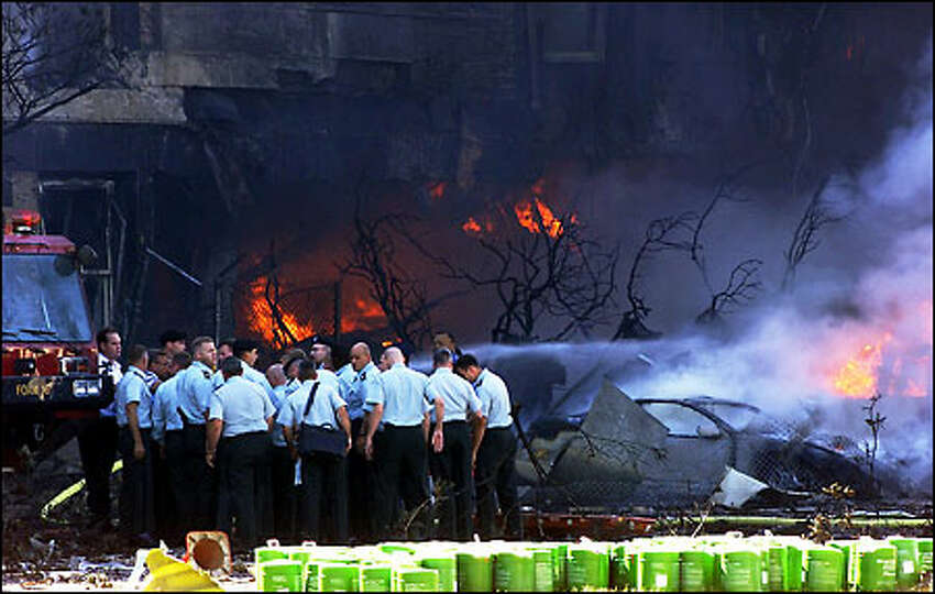 Emergency personnel assess the situation at the Pentagon in Washington after an aircraft crashed into the building on Sept. 11, 2001. (AP Photo/Hillery Smith Garrison)