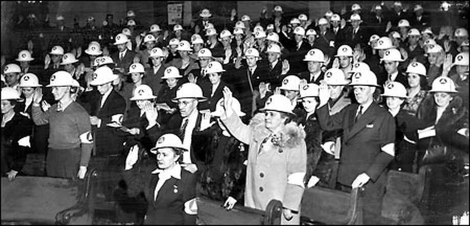 Home front helpers, 1943: Donning helmets and armbands. Seattle's largest-ever class of air raid wardens - 407 members - takes the official oath at Queen Anne Methodist Church. The Office of Civilian Defense trained such volunteers to help put out lights during blackouts and get medical help in case of an attack. P-I photo by Stuart Hertz Photo: Seattle Post-Intelligencer