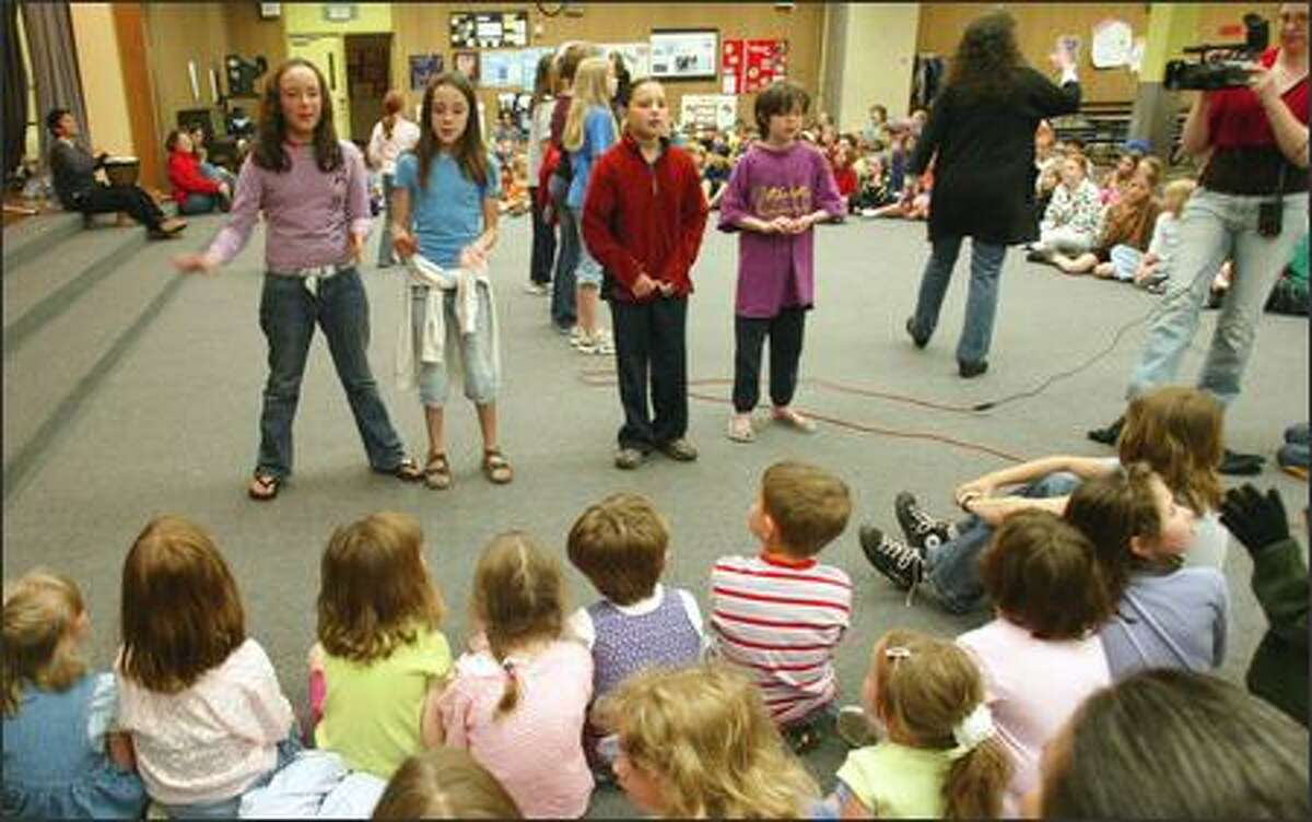 Mary K. McNeill leads elementary school children through songs of peace at Salmon Bay Elementary School on Friday.