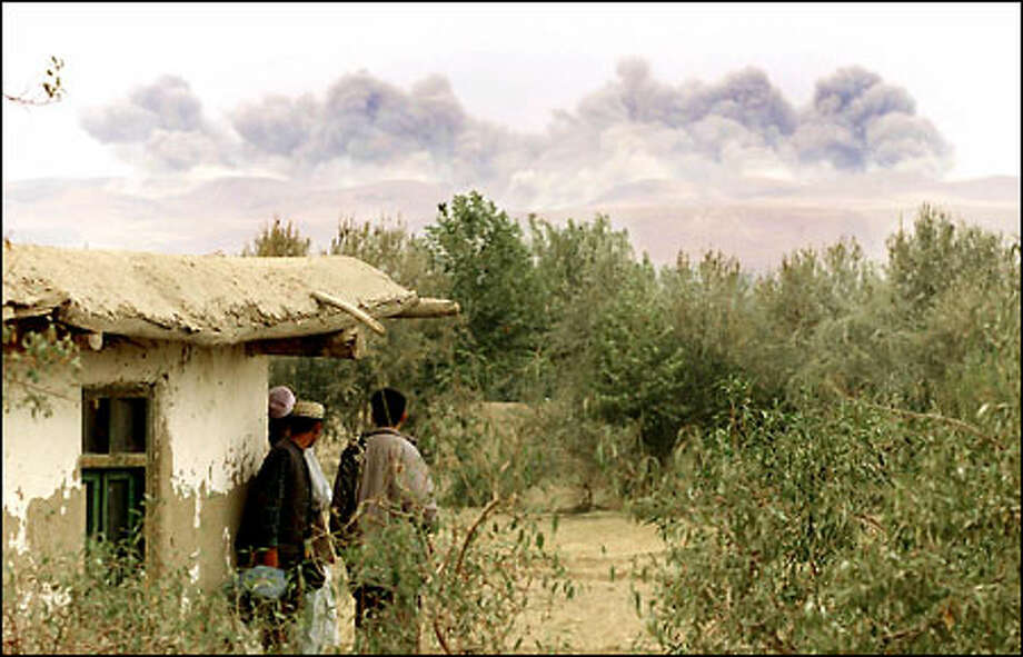 Residents of Dasht-e-Qhaleh, Afghanistan watch the result of carpet bombing by U.S. B-52s about two miles from their town near the Tajikistan border. Photo: Joshua Trujillo, Seattlepi.com