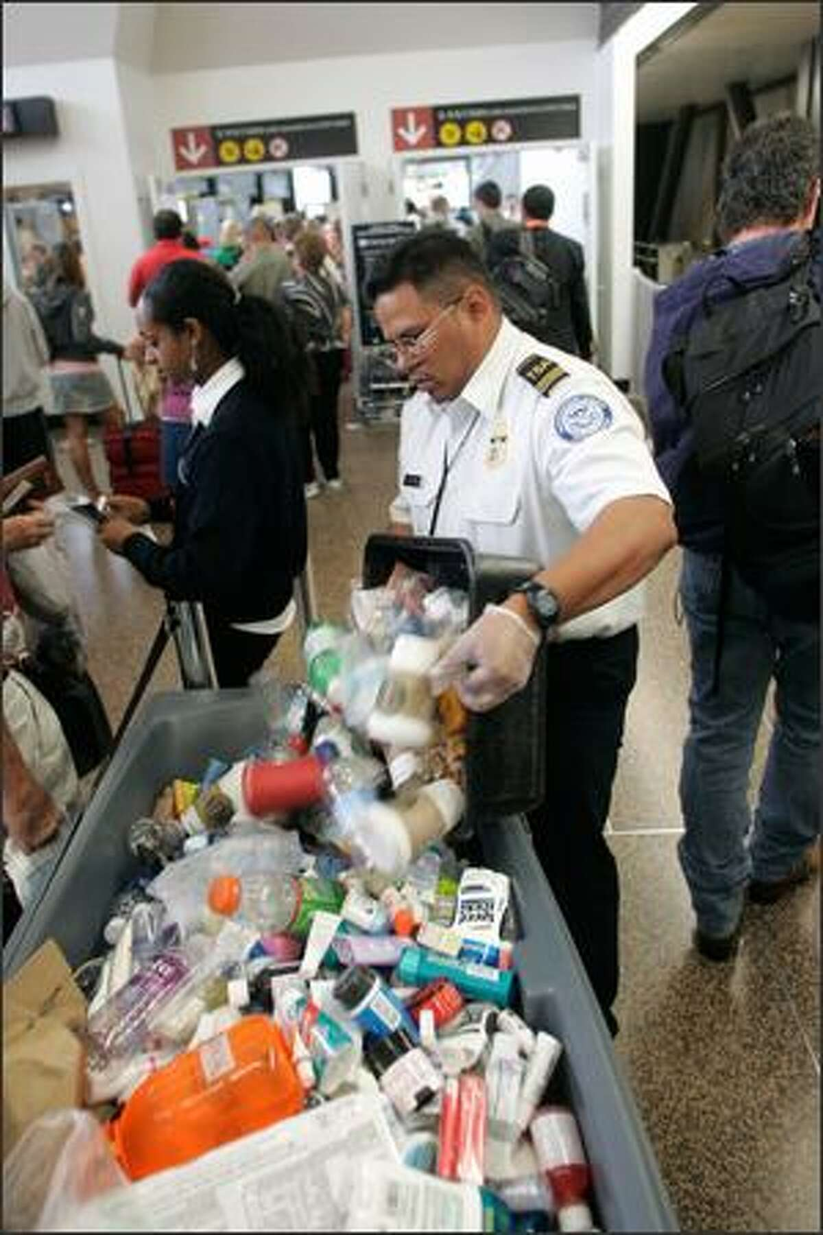 A Transportation Security Administration employee dumps a box containing items no longer permitted on board aircraft -- including beverages, toothpaste, shampoo, deodorant sticks and other such liquids and gels. New restrictions on carry-on luggage were imposed Thursday morning after British authorities thwarted a terrorist plot to blow up airliners headed for the United States using liquid explosives smuggled onto flights.