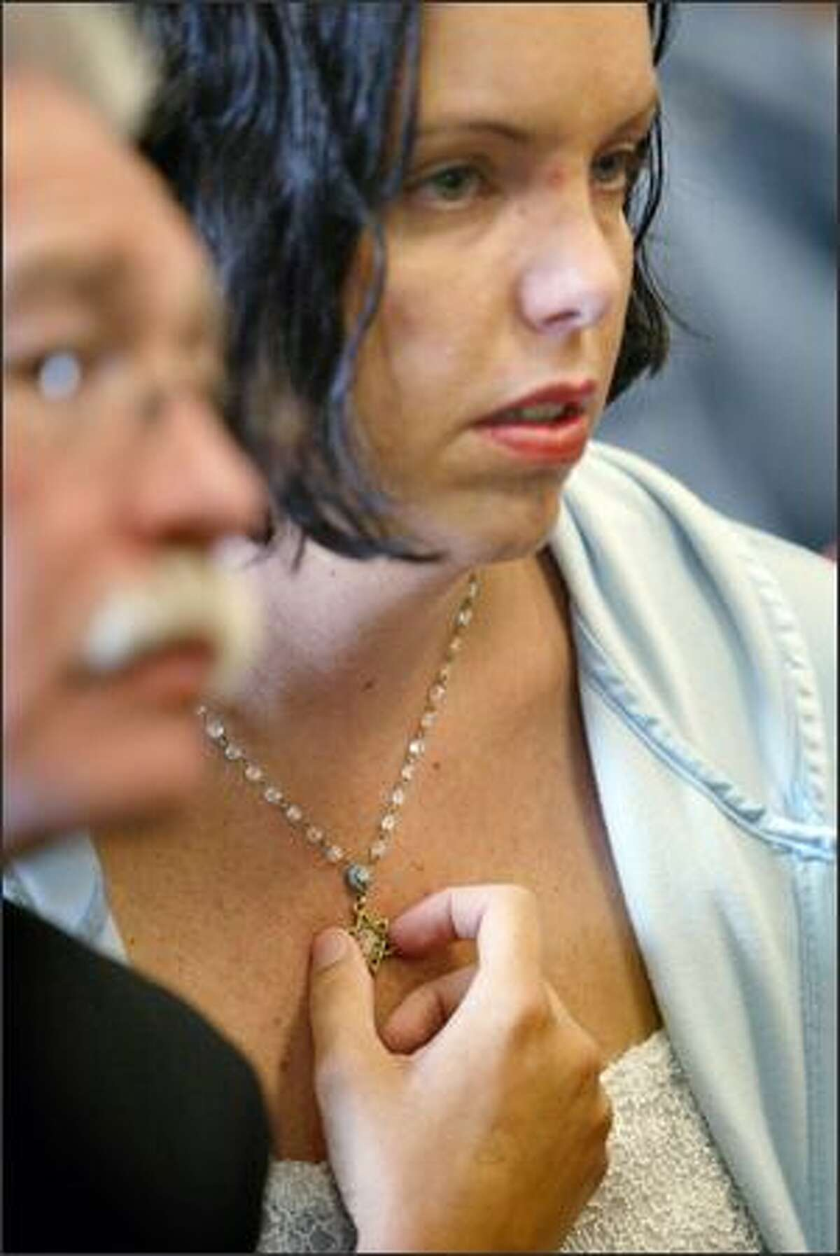 Tammy Kaiser, the employee of the Jewish Federation of Greater Seattle who fled the shooting by jumping through a window, touches her Star of David pendant during the arraignment for Naveed Haq at the King County Courthouse in Seattle on Thursday.