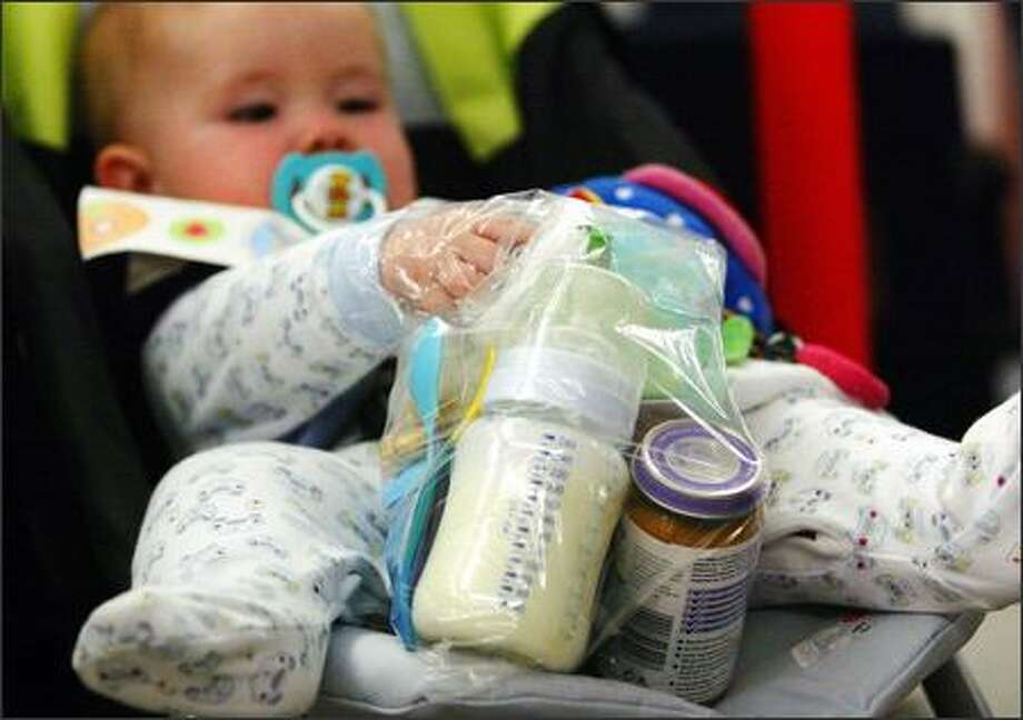 A baby holds onto a plastic bag filled with baby formula and food at Edinburgh airport, in Scotland, Thursday. Officials raised security to its highest level -- suggesting a terrorist attack might be imminent -- and banned hand-carried luggage on all trans-Atlantic flights. Huge crowds formed at security barriers as officials searching for explosives barred nearly every form of liquid outside of baby formula. (AP Photo/David Cheskin,PA) Photo: Associated Press