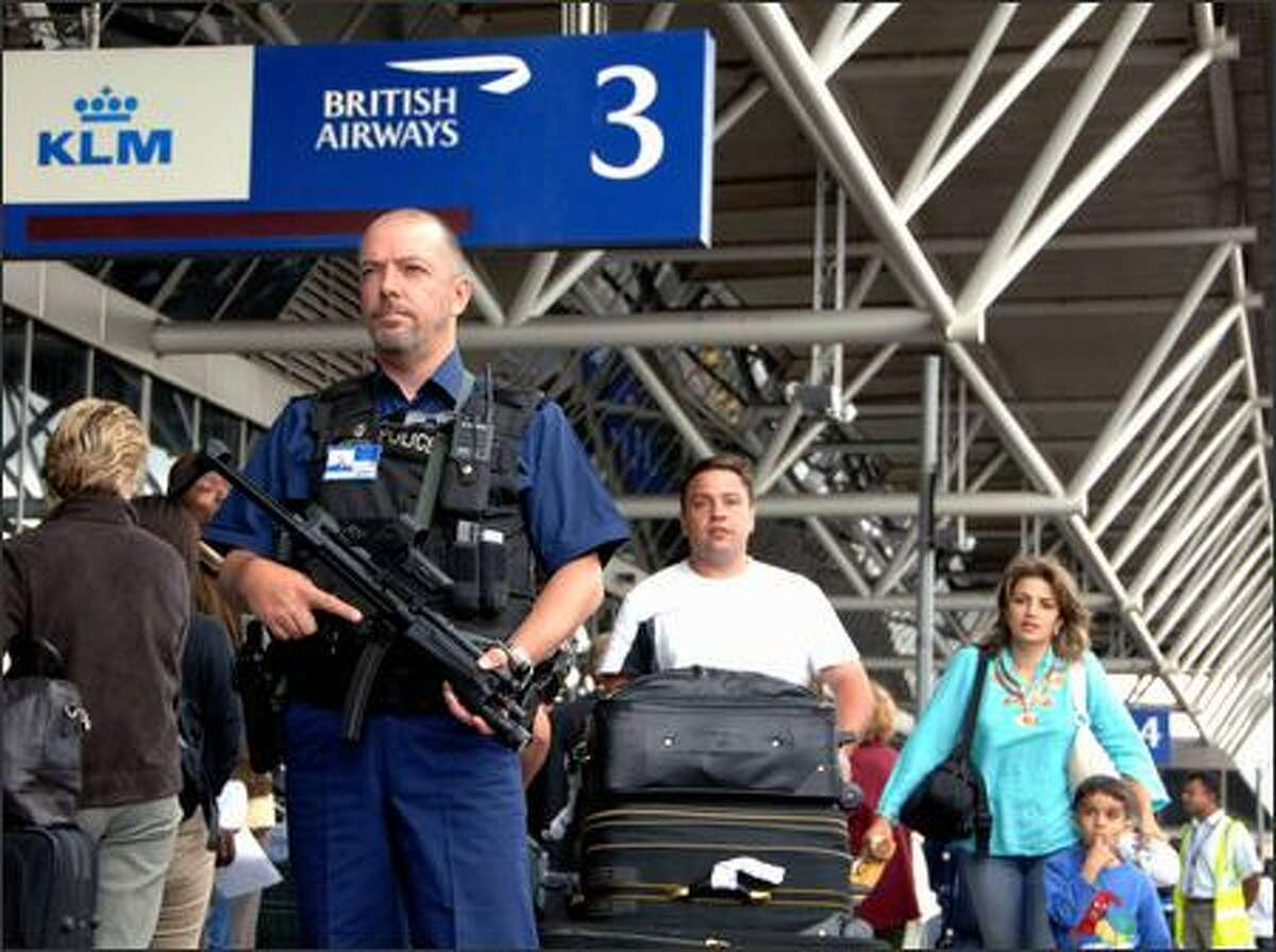 A police officer patrols Thursday at London's Heathrow airport. Security was raised to its highest level and carry-on items were banned.