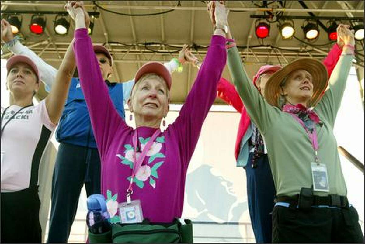 From left to right, breast cancer survivors Ellen Gonser, Karen Baer and Megan Neill join hands before leading the way for some 2,700 participants in the Breast Cancer 3-Day walk, which started Friday in Marymoor Park. The walk, which raised $6.9million, ends Sunday near Husky Stadium.