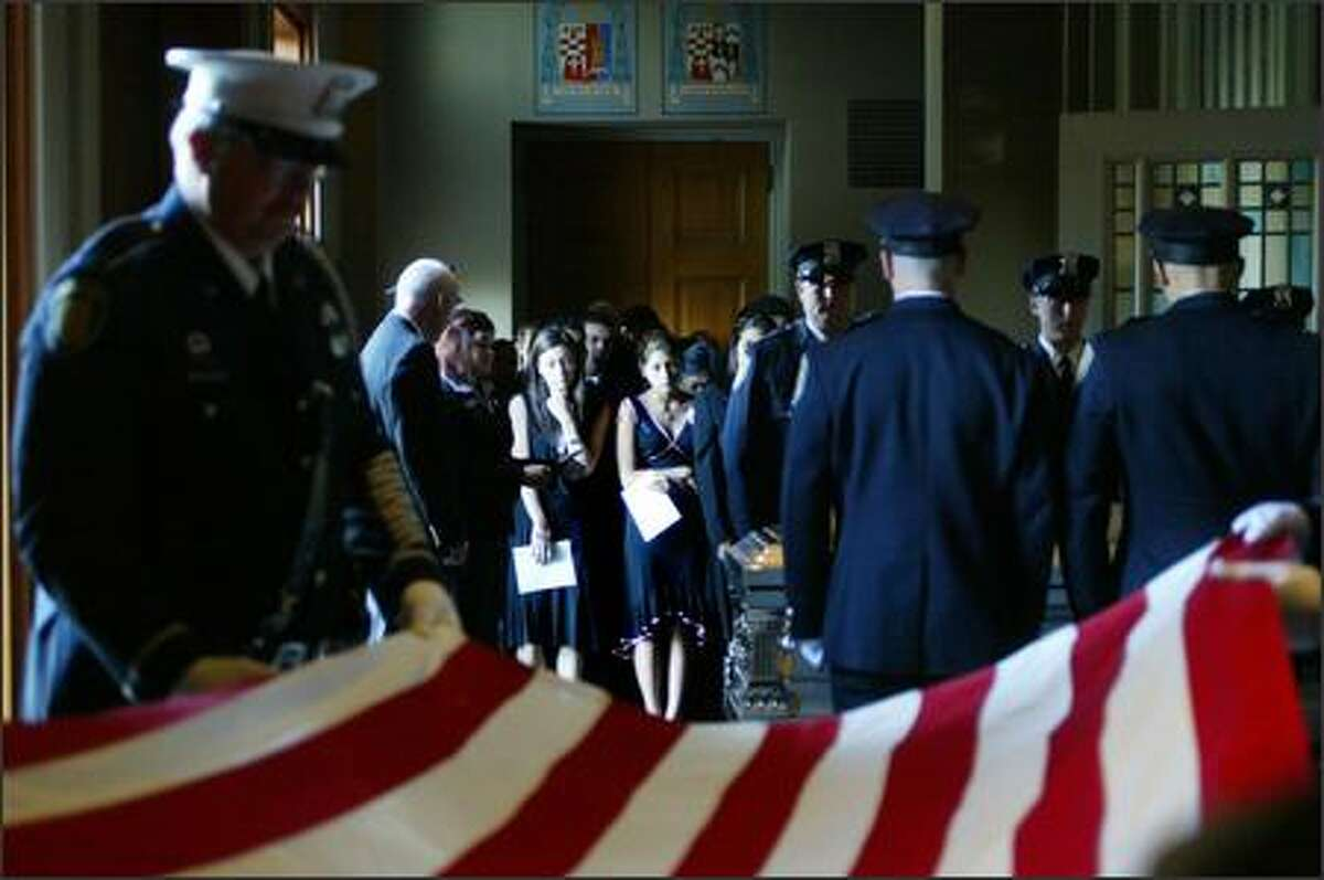 An American flag is taken off the casket of Seattle police officer Joselito Barber at the start of his funeral at St. James Cathedral. Family members, including his fiancé, Amber Noel-Du, left, and his sister, Emily Rio Barber, watch.
