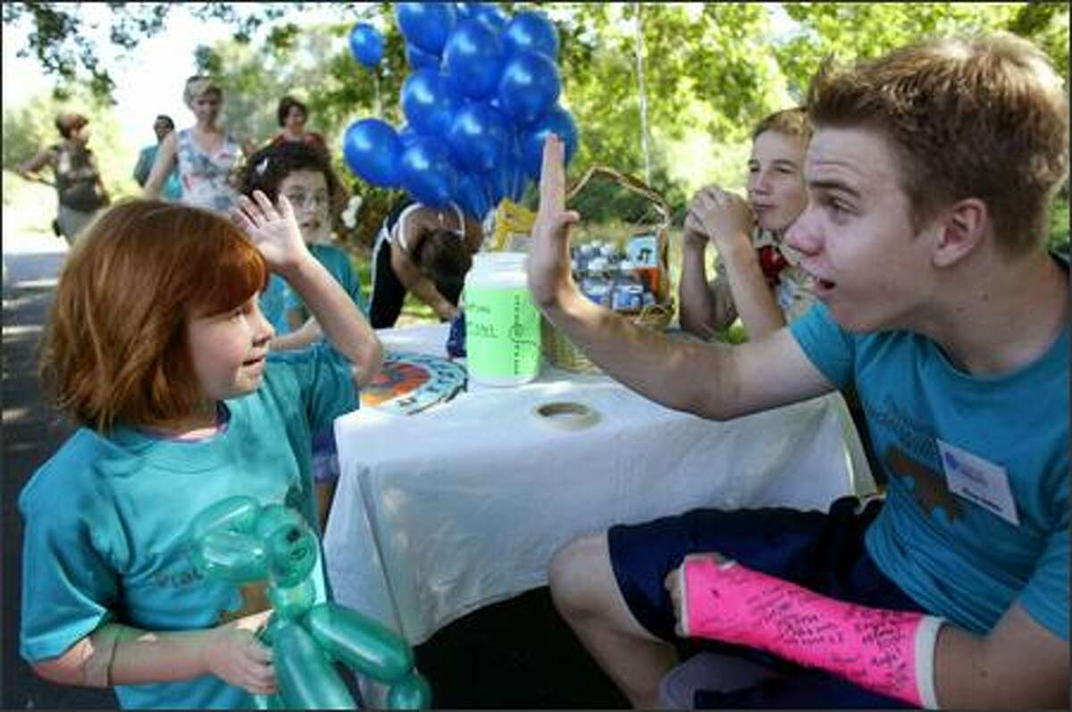 Ryan Johns, a volunteer, gives Hannah Leigh a high five at the halfway point of the Foundation for Prader-Willi Research walk on Aug. 26 in Bothell.