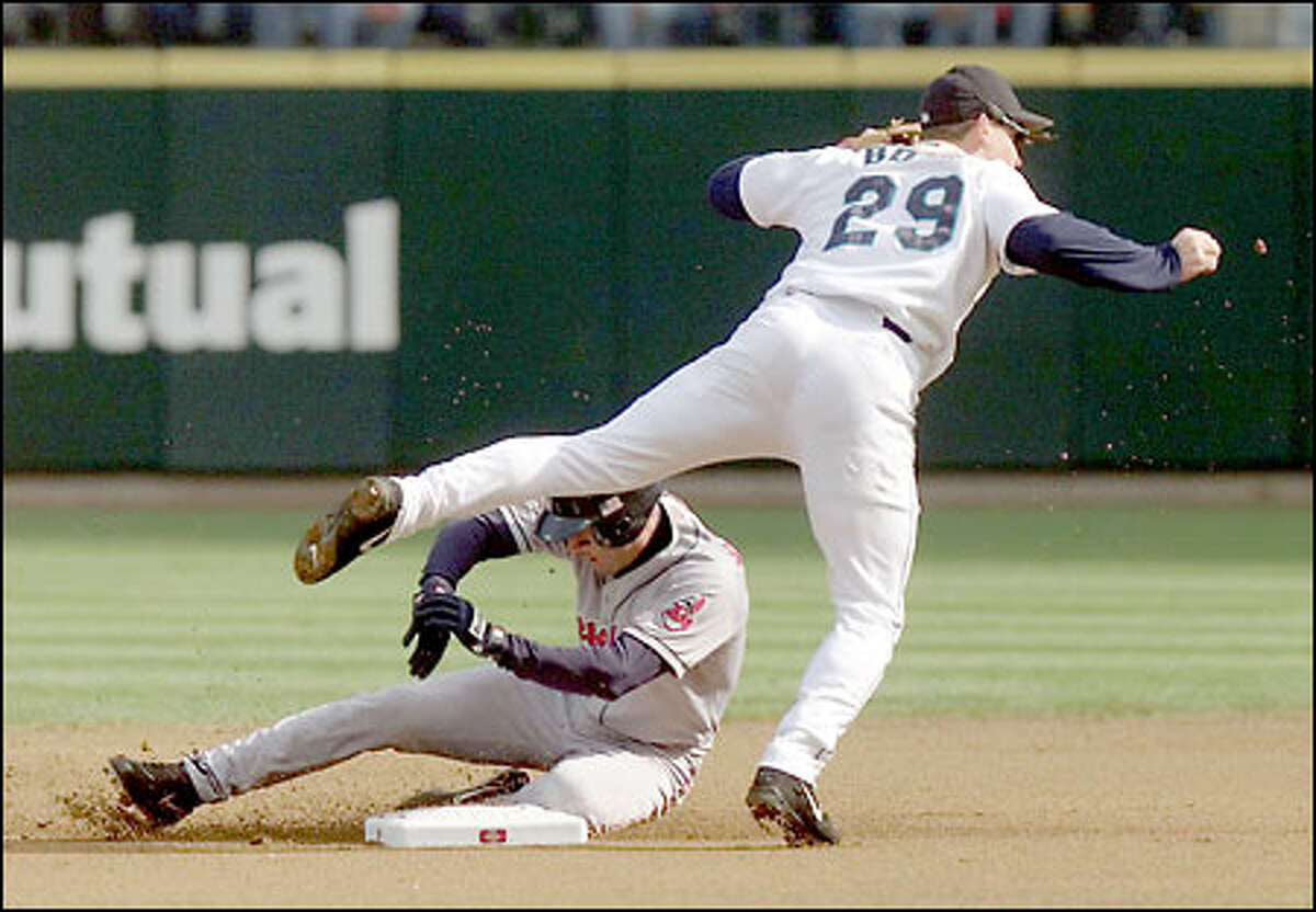 Cleveland Indians shortstop Omar Vizquel slides into second base a moment too late as Mariners second basement Bret Boone relays the ball onto first base for a double play to end the first inning.