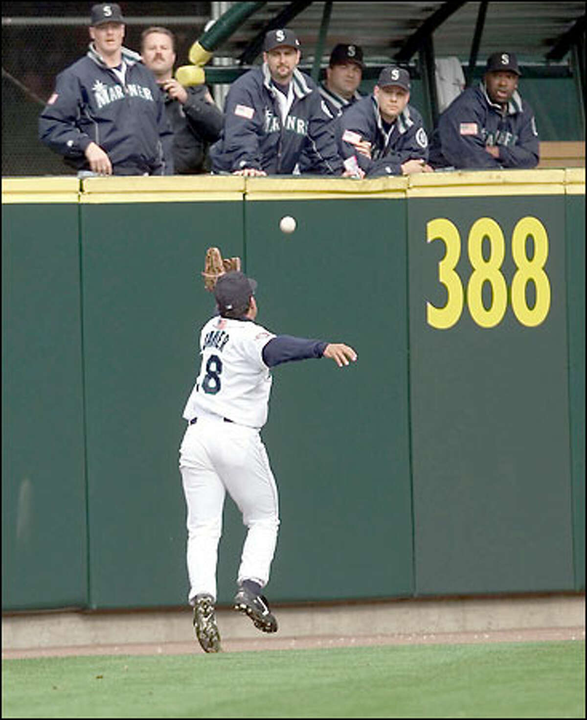 As the Mariners bullpen looks on, Stan Javier races after a deep-hit double by the Indians' Travis Fryman. Fryman later scored Cleveland's first run of the game on a single by Kenny Lofton.