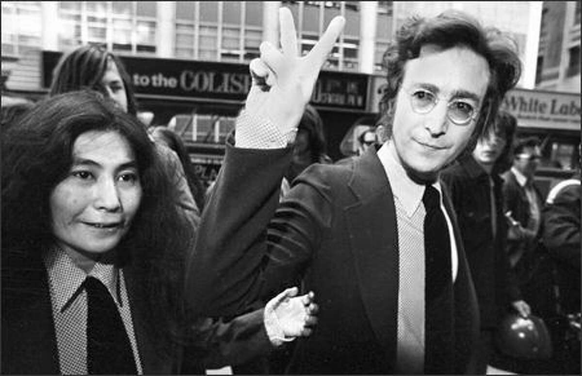 Former Beatle John Lennon, giving the peace sign, and his wife, Yoko Ono, arrive for a hearing on their deportation case at U.S. Immigration and Naturalization Service office in lower Manhattan, on May 12, 1972. The ex-Beatle's celebrated battle with the feds is chronicled in