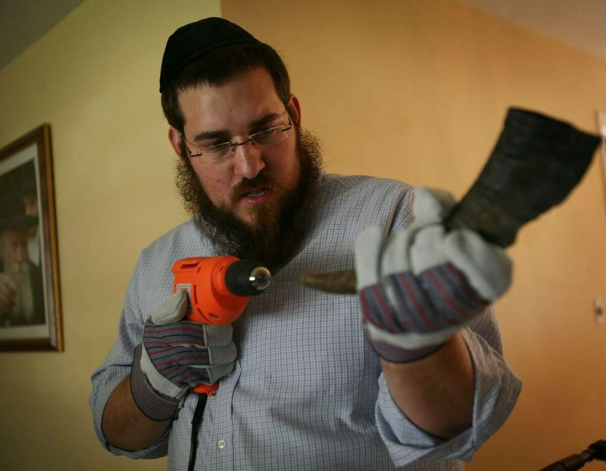 Rabbi Shlame Landa drills through the solid tip of a ram's horn as he demonstrates the making of a Shofar in his home on Thursday, September 10, 2009 in Fairfield, Conn.