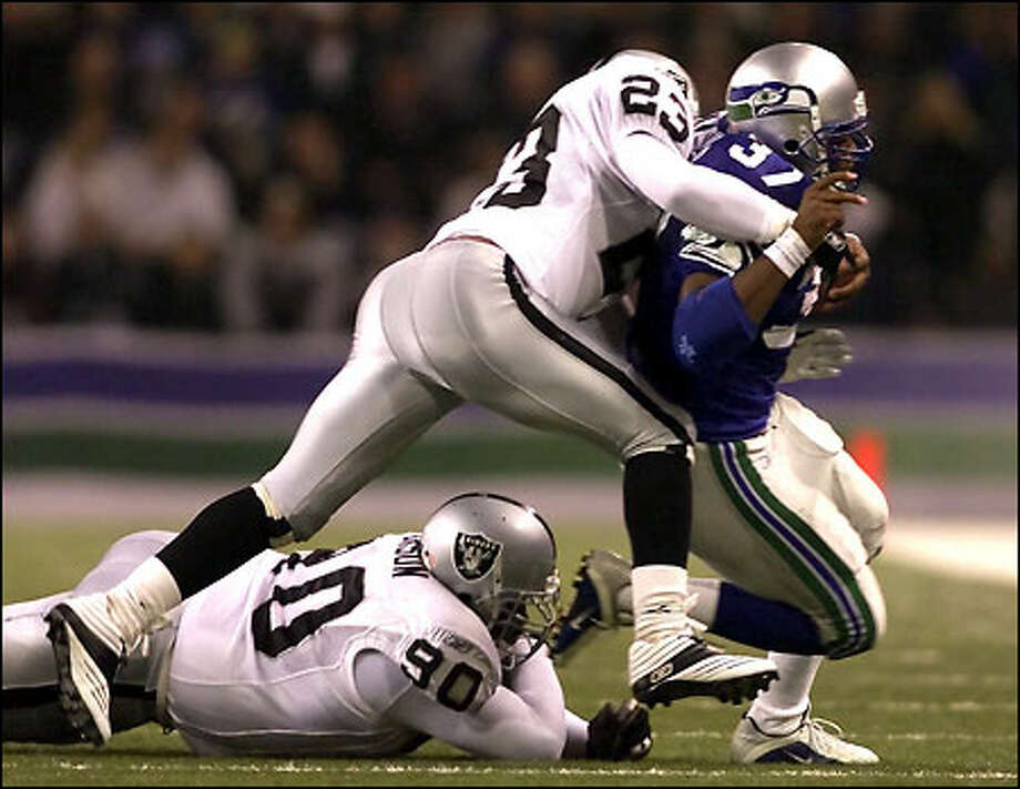 Seahawks' Shaun Alexander makes a gain of four yards with Raiders' Marquez Pope on his back with 10.30 minutes left in the second quarter at Husky Stadium. Photo: Mike Urban, Seattle Post-Intelligencer
