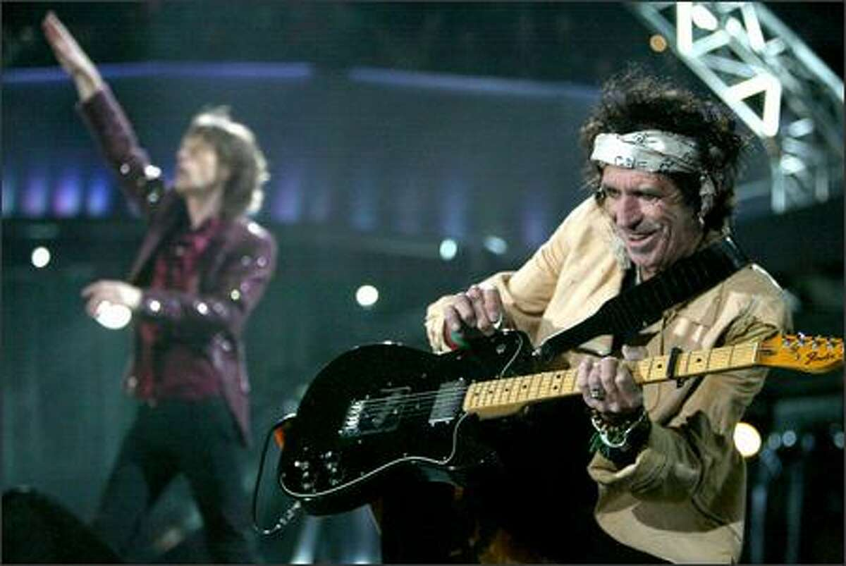 Rolling Stones guitarist Keith Richards (right) appears to be enjoying the opening moments of Tuesday night's show at Qwest Field while lead singer Mick Jagger pumps up the house.