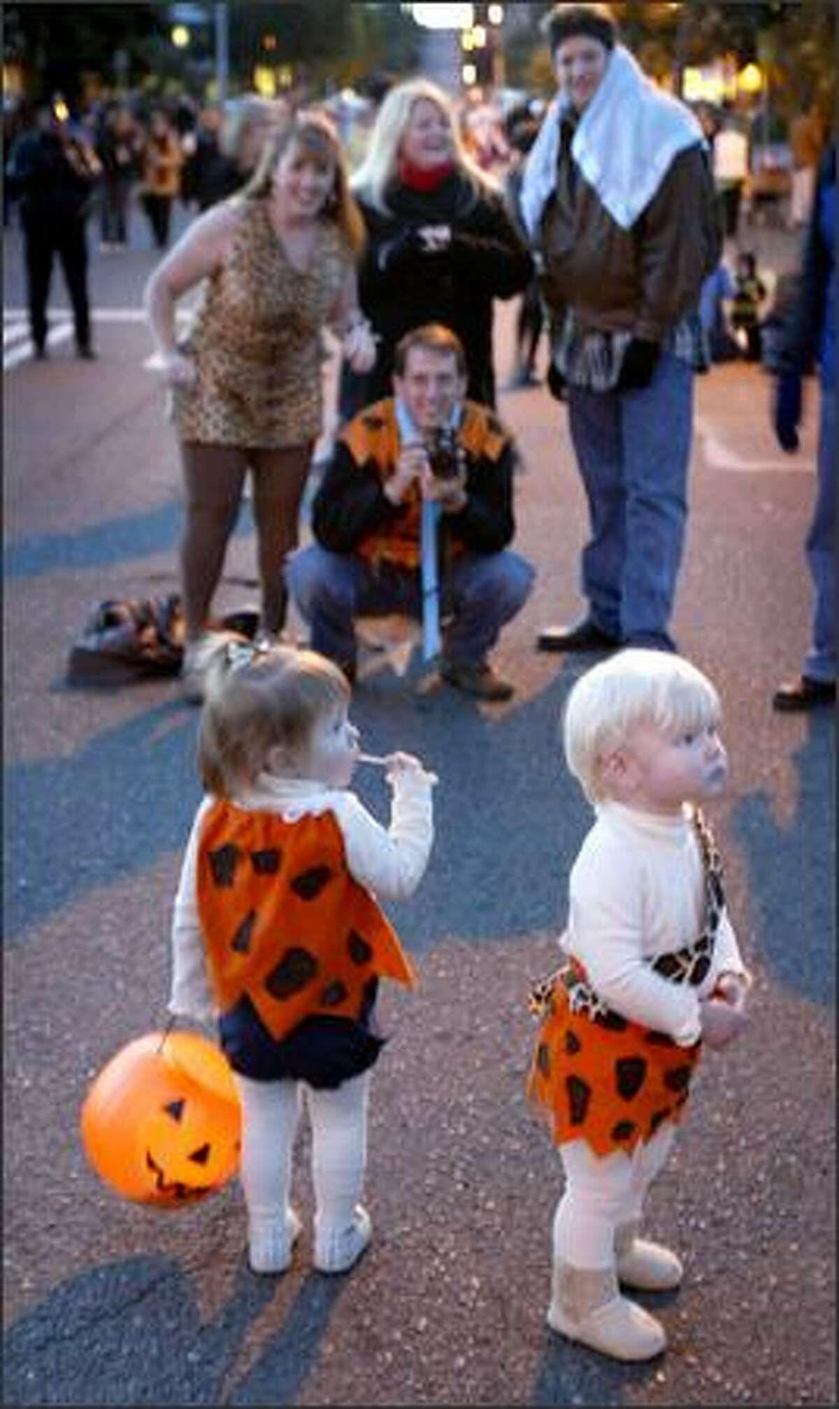 Cecilia Phillips, 1, left, and Jabe Wesson, 1, check out the scene while their family tries to take a photo of the young Flintstones in Magnolia Village during the annual neighborhood trick-or-treat event on Tuesday in Seattle. Hundreds of little ghosts, golblins, ferries, monsters and a few Darth Vaders invaded the quiet neighborhood in search of Halloween treats.