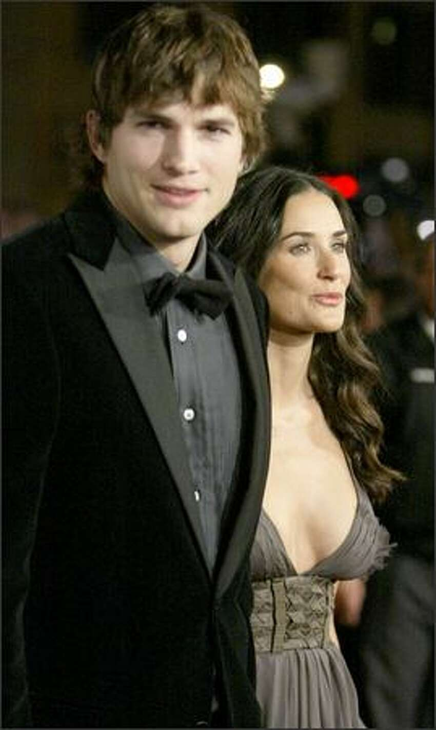 Ashton Kutcher, left, and Demi Moore, right, arrive for the premiere of the movie