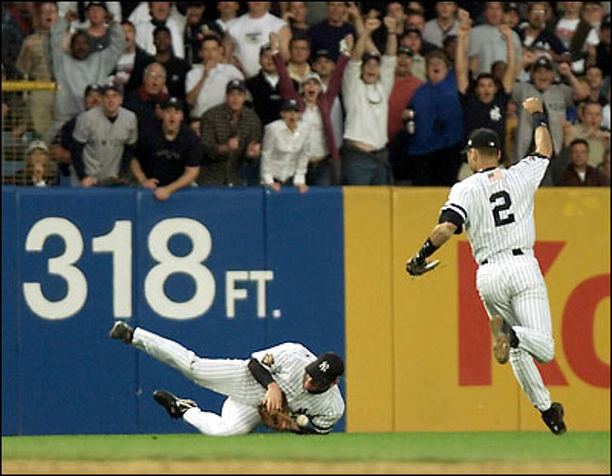 Yankee Chuck Knoblauch drops the ball while Derek Jeter makes the