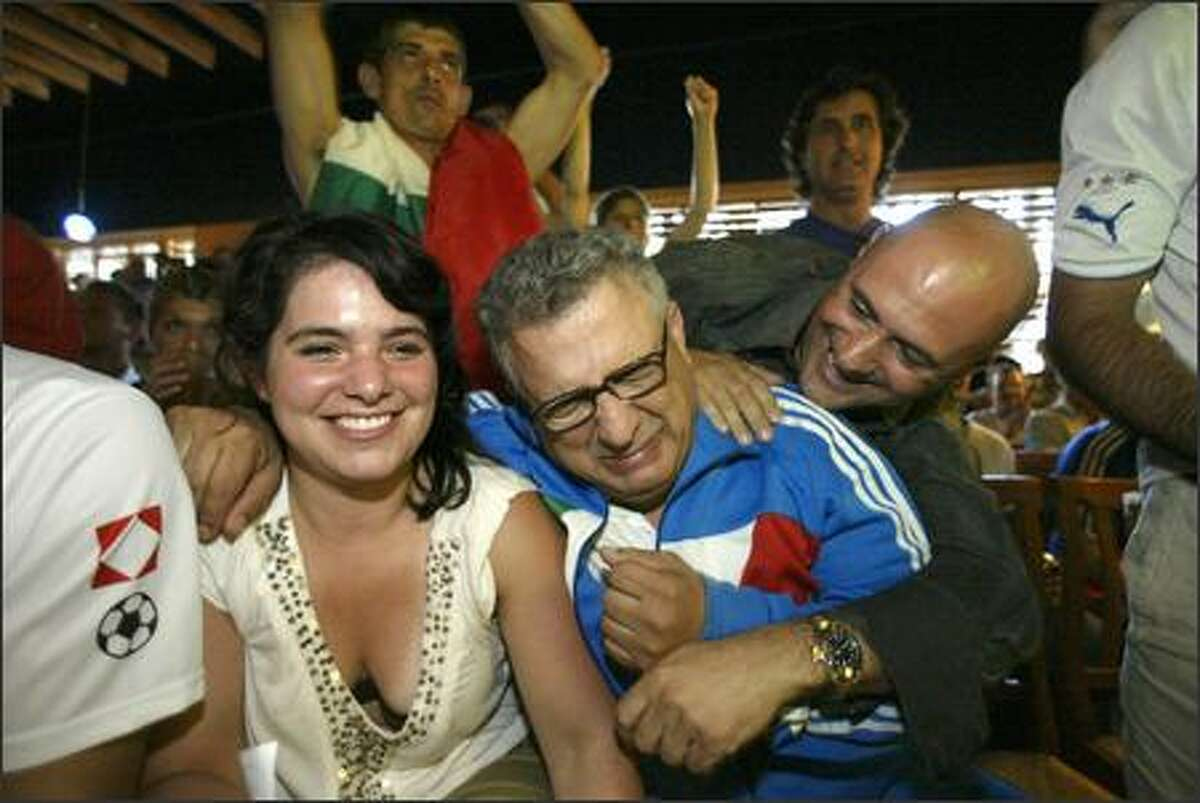 Mario Vellotti, center, hugs Anna Derr, left, as another Italian fan teases him inside the La Vita e Bella restaurant after they watched Italy beat France 5-3 in a penalty shootout for the World Cup.