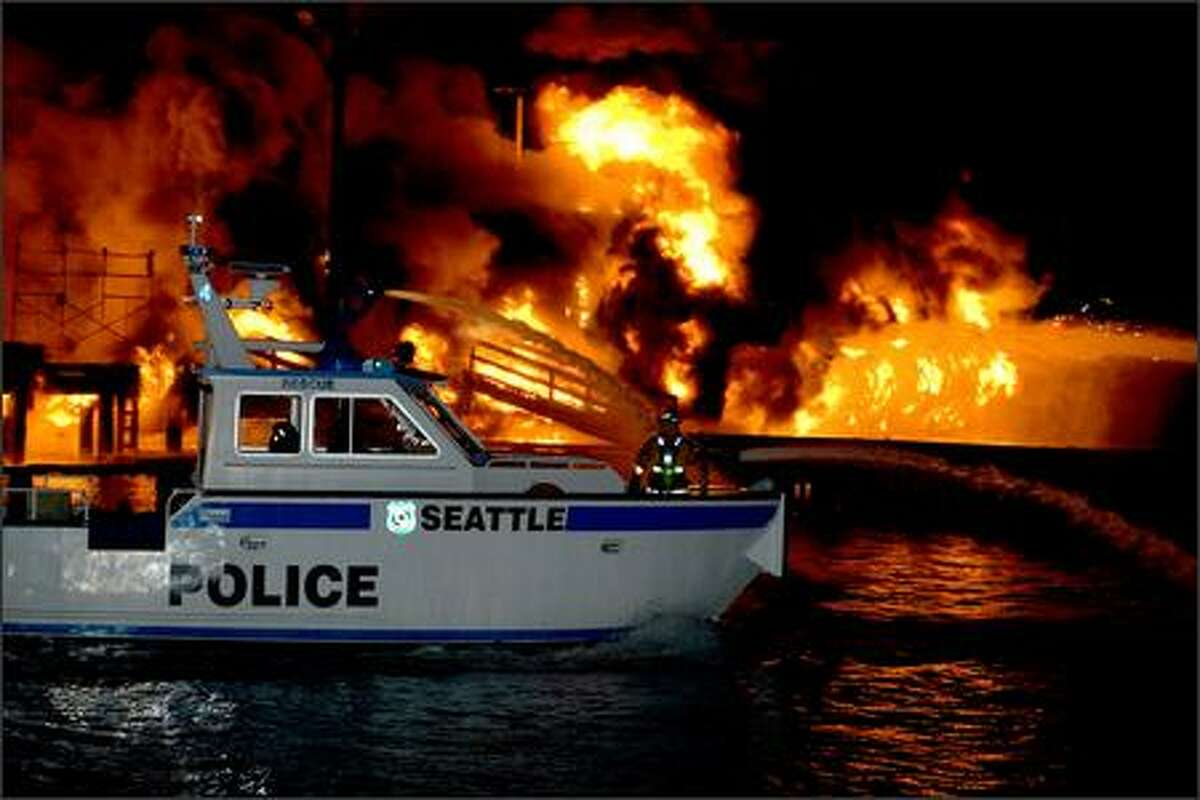 Towering flames light up the night sky from a massive fire on Lake Union. Emergency crews received the call at 1:28 a.m., said Helen Fitzpatrick, Seattle Fire Department spokeswoman.