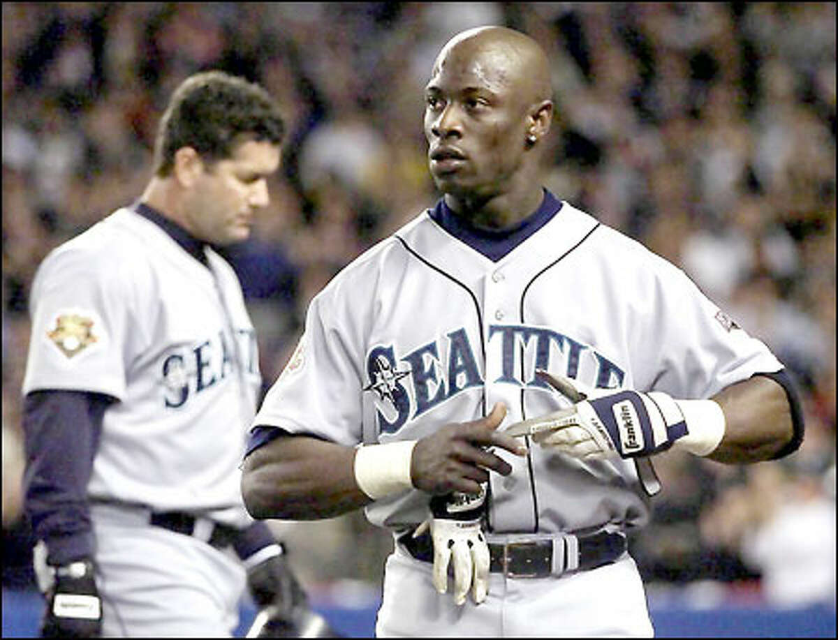 Mike Cameron takes his gloves off after Edgar Martinez popped out, stranding Cameron at second base in the first inning. Martinez did not have a hit with men in scoring position in the ALCS.