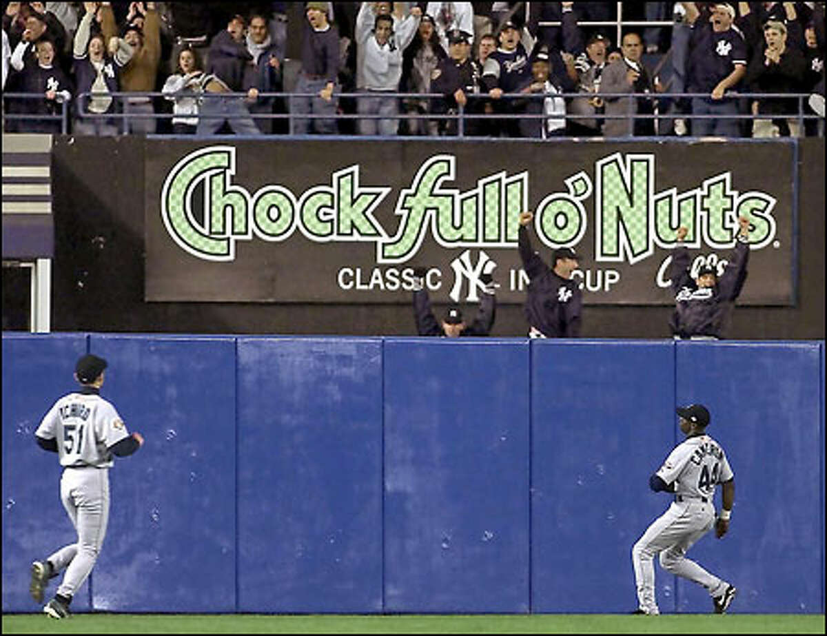 Ichiro and Mike Cameron watch Bernie Williams' home run go over the fence in the third inning.