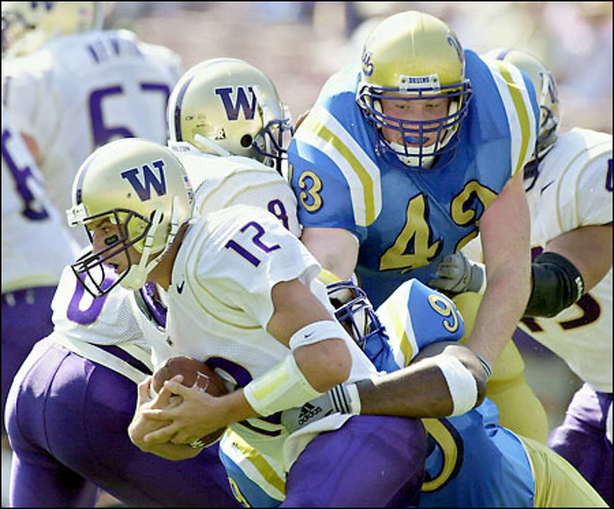 Washington quarterback Taylor Barton is sacked by UCLA's Kenyon Coleman (99) and Dave Ball (43) in the second quarter.