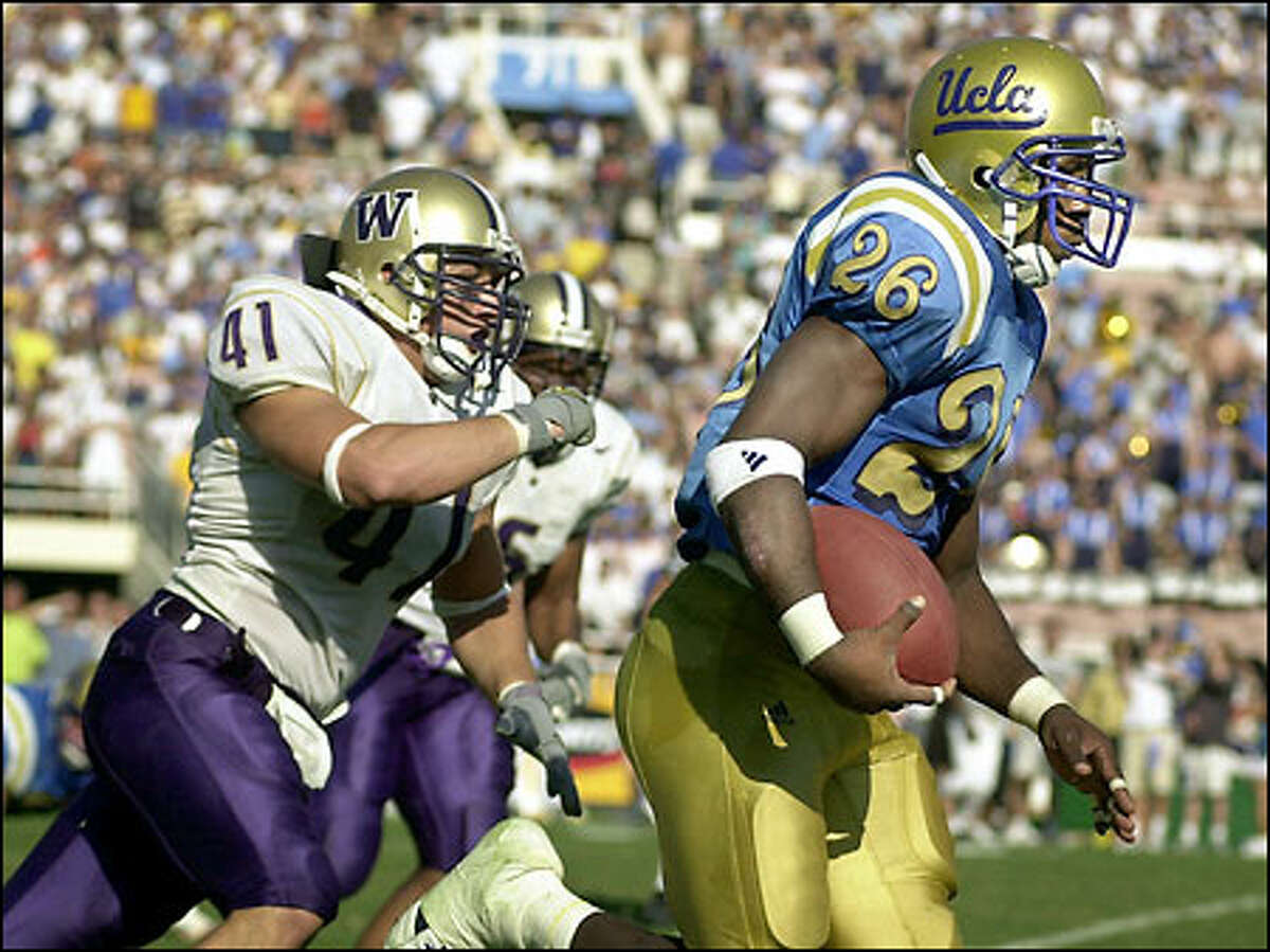 UCLA tailback DeShaun Foster outruns Washington linebacker Ben Mahdavi (41) as he takes off on a 92-yard touchdown run in the fourth quarter. Foster ran for a school-record 301 yards and four touchdowns.