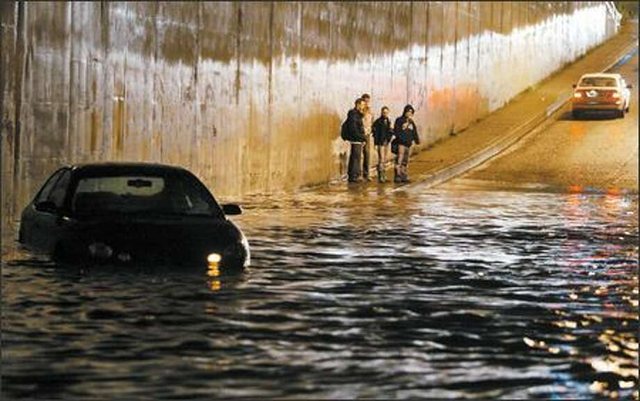 People look back at a car stalled in high water in the Aurora Avenue underpass on Mercer Street on Thursday as another car turns around to avoid four feet of water. Two cars were stuck. Numerous other cars passed through the water ignoring the deep water. Photo: Joshua Trujillo, Seattlepi.com