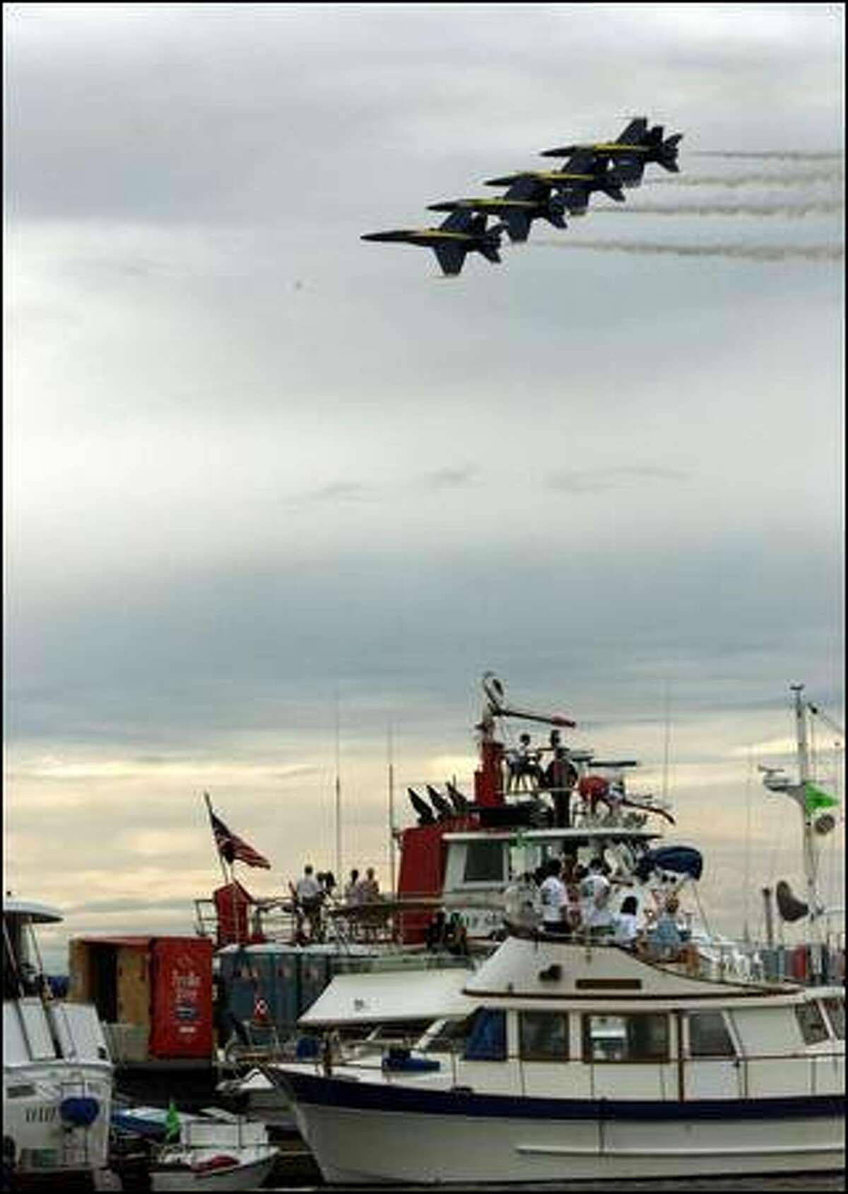 The Blue Angels entertain spectators aboard boats on Lake Washington as part of the Seafair festivities.