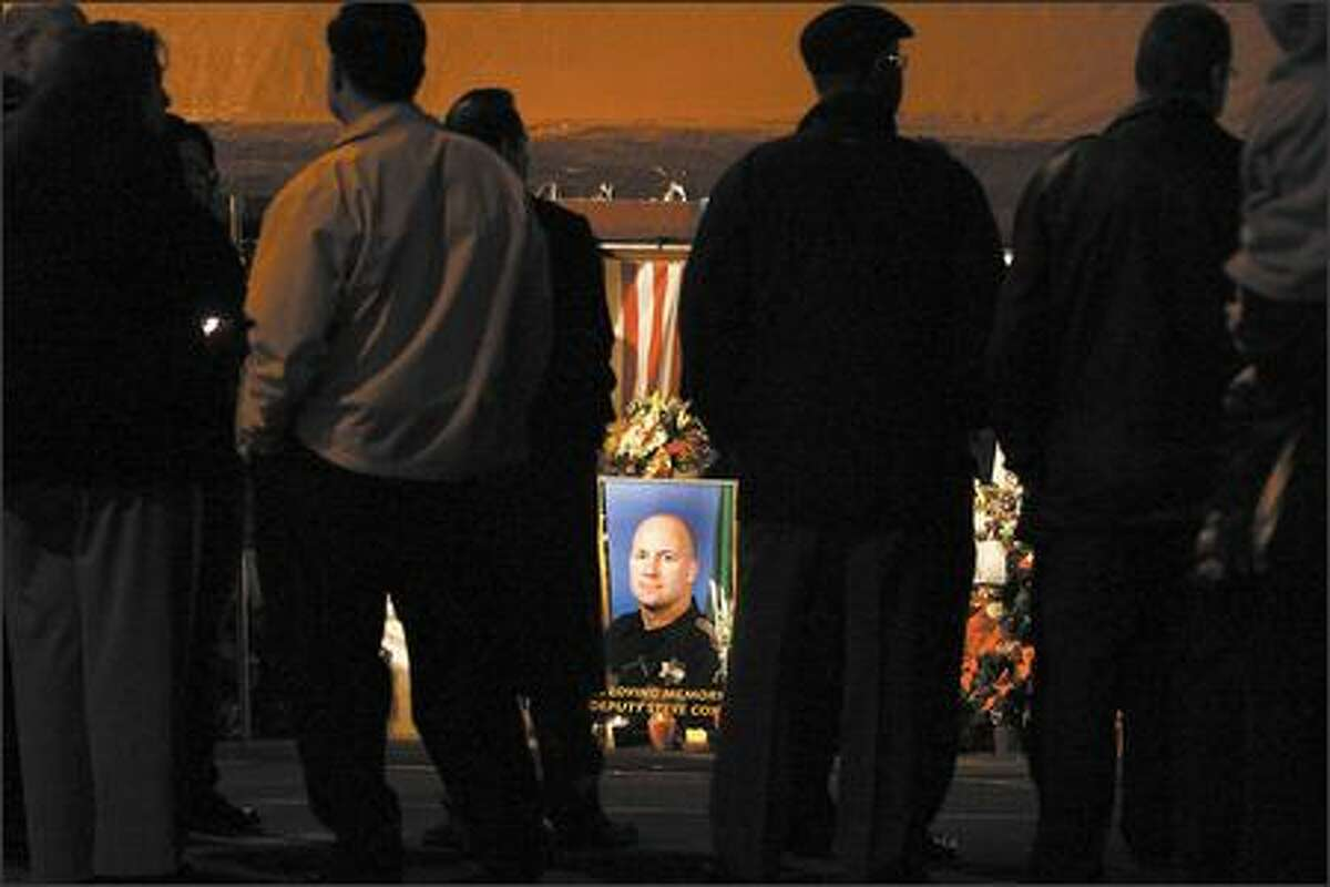 A portrait of Steve Cox stands out as hundreds attend a candlelight vigil and service that were held in front of the King County Sheriff's sub-station in White Center for slain King County Sheriff's Deputy Steve Cox on Tuesday.