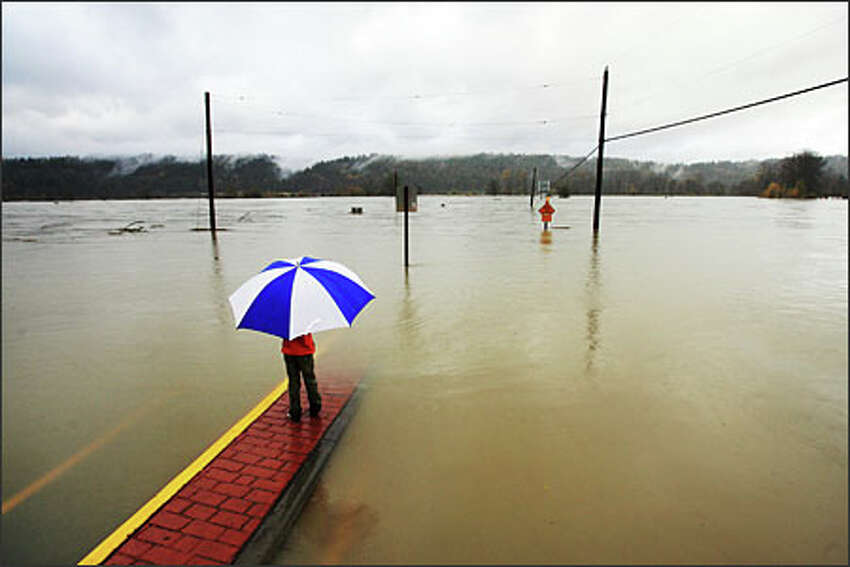 Gillian May, 7, watches the Snoqualmie River, which passed over Northeast 124 Street in Duvall.