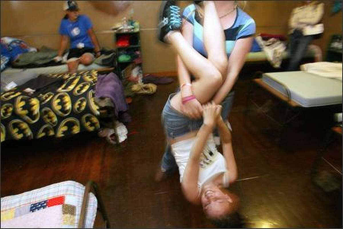 Lisa Williamson is hung upside down by fellow camper, Kayla Larsh, 17, from Sumner, as they play around in their cabin at Camp Eyabsut.