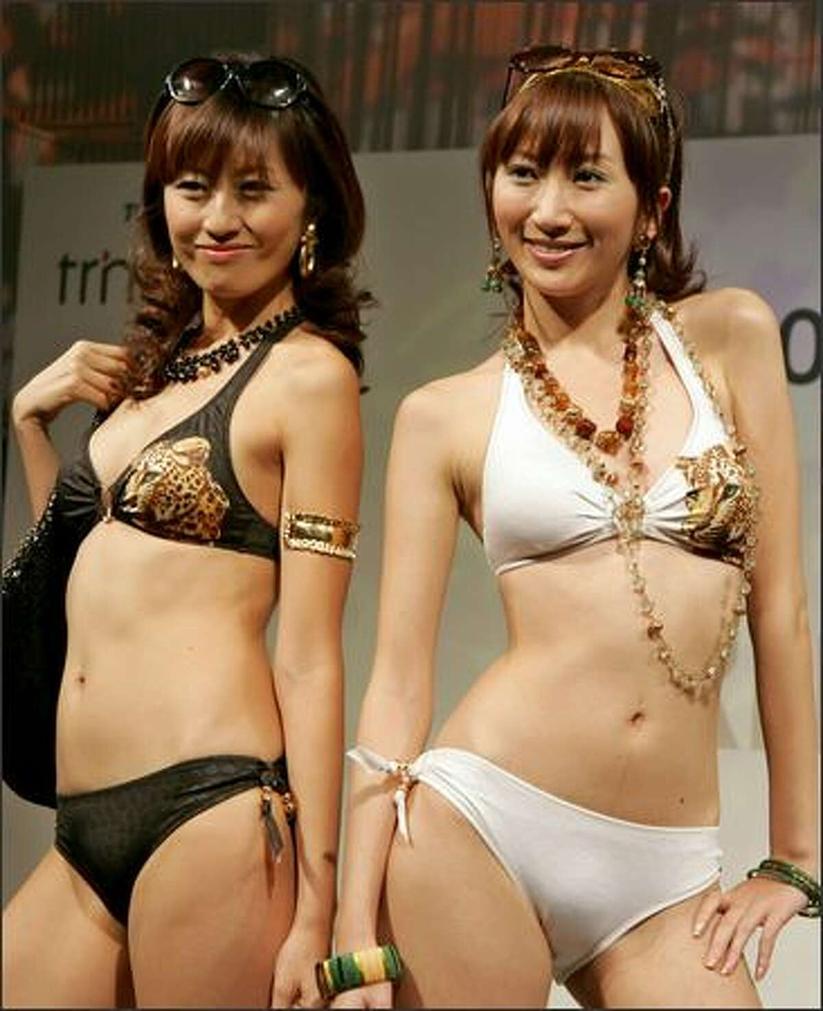 Models smile in bikinis during the 2007 swimwear collection presented by Japan's Toray Industries Inc. in Tokyo on Monday. The Tokyo-based materials producer offers its latest beachwears using the quick-drying, everlasting and sandproof textile applied by its own cutting-edge nano technology called