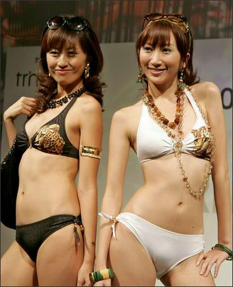 "Models smile in bikinis during the 2007 swimwear collection presented by Japan's Toray Industries Inc. in Tokyo on Monday. The Tokyo-based materials producer offers its latest beachwears using the quick-drying, everlasting and sandproof textile applied by its own cutting-edge nano technology called ""NanoMATRIX."" (AP Photo/Koji Sasahara)"