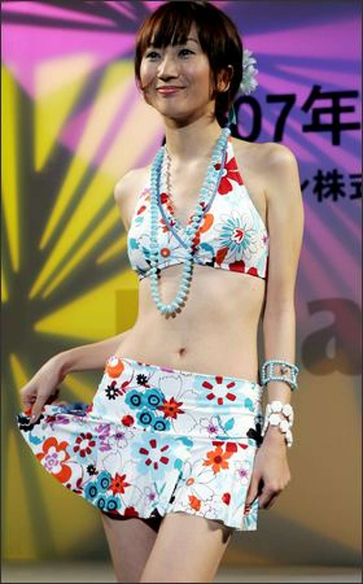 A model smiles in separates during the 2007 swimwear collection presented by Japan's Toray Industries Inc. in Tokyo on Monday. The Tokyo-based materials producer offers this year its latest beachwears using the quick-drying, everlasting and sandproof fabric applied by its own cutting-edge nano technology called