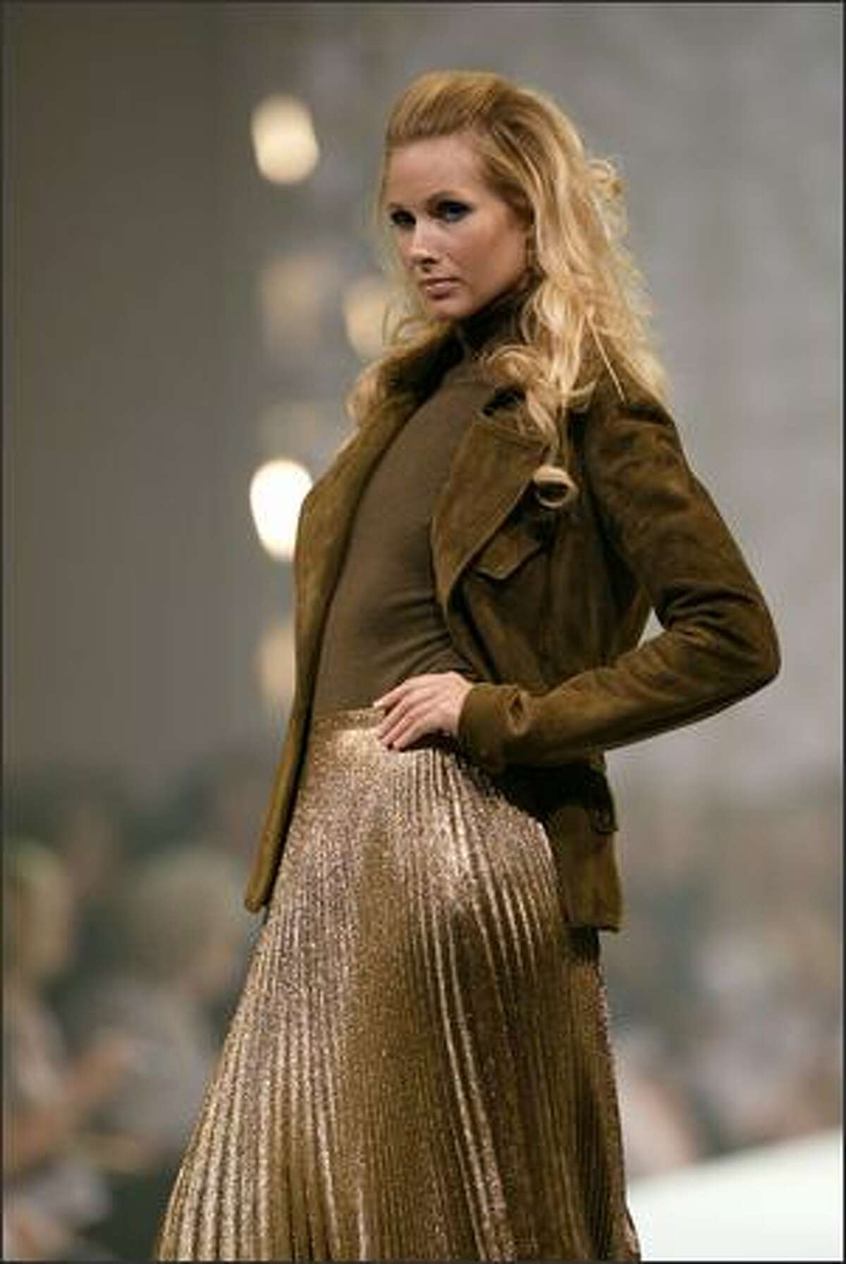 Ralph Lauren does his earth-toned thing with an olive suede double-breasted jacket and moss cashmere turtleneck. We see two strong trends (gold lame and pleats) in the skirt.