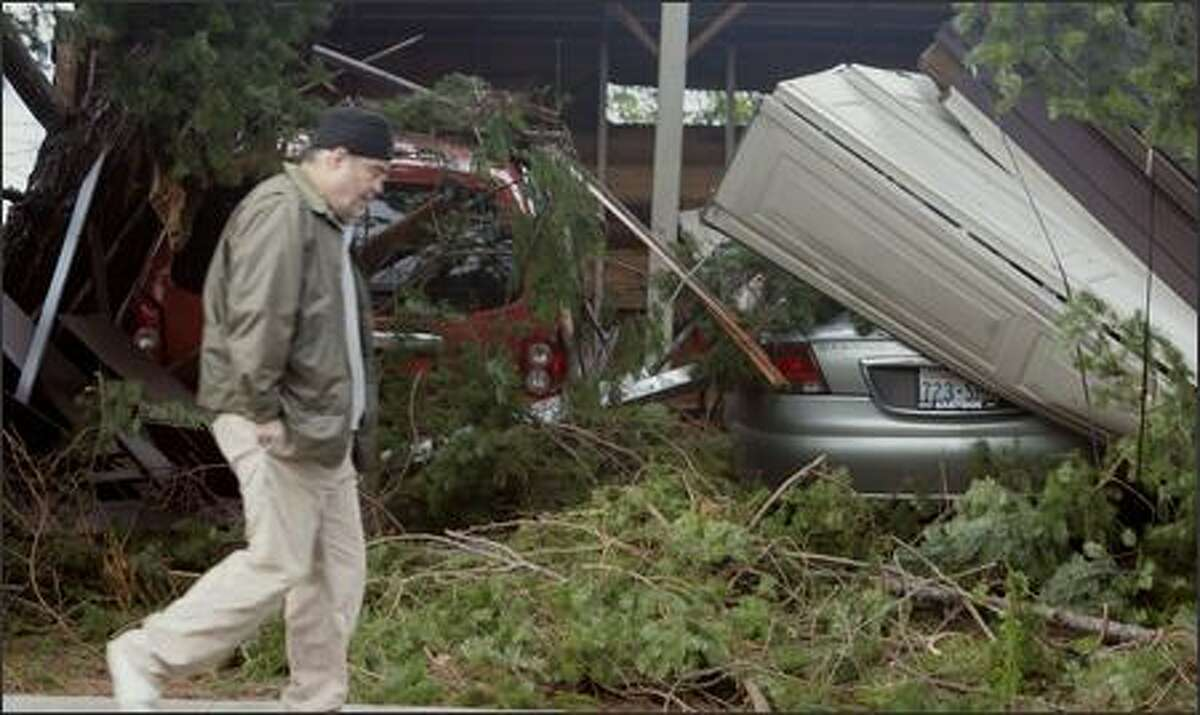 John Roberts walks past a neighbor's garage which was crushed by a falling tree earlier in the morning, Friday, Dec. 15, 2006, in Seattle. A one-two punch of howling windstorms and heavy rains left at least three people dead and more than 1 million homes and businesses without power across Western Washington early Friday. (AP Photo/Elaine Thompson)
