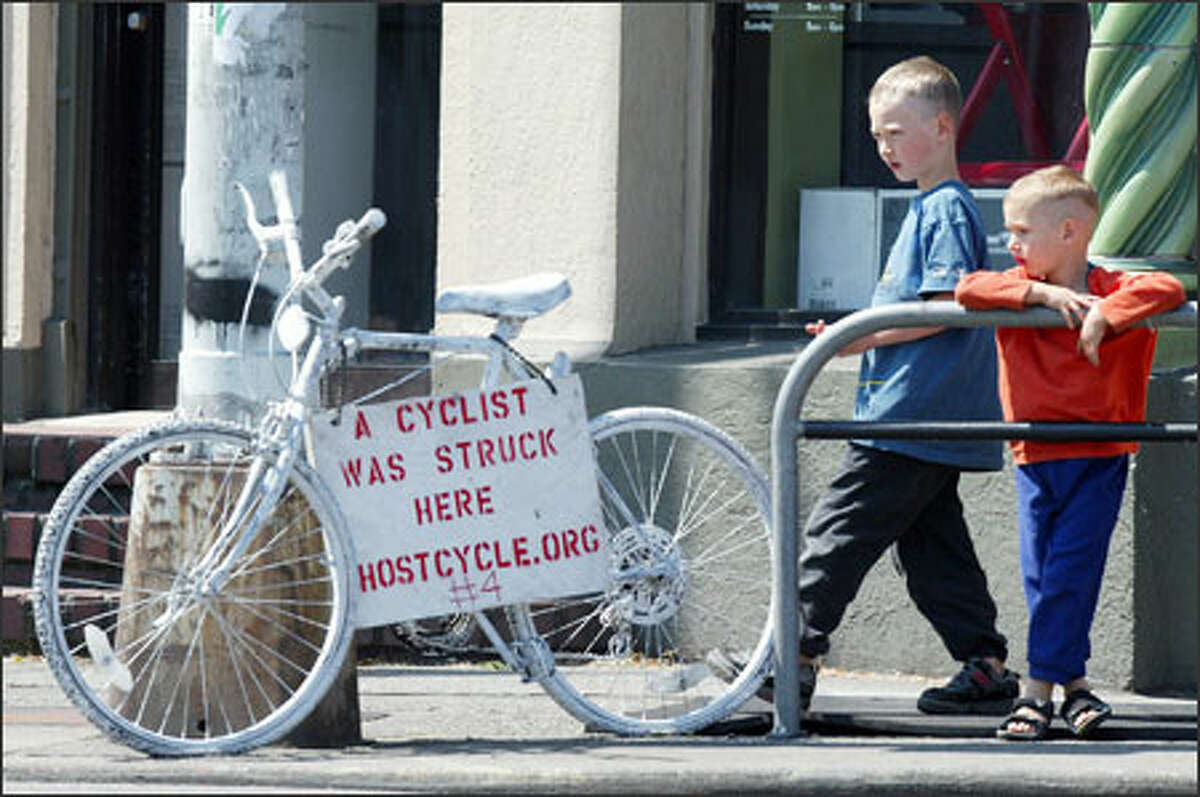 """Alex, 6, and Amiel Richter, 3, check out a """"ghost bike"""" marking a spot at Roosevelt Way Northeast where a bicyclist was hurt in an accident with a car. Their father, Ingo Richter, says he also was hurt in a bike accident."""