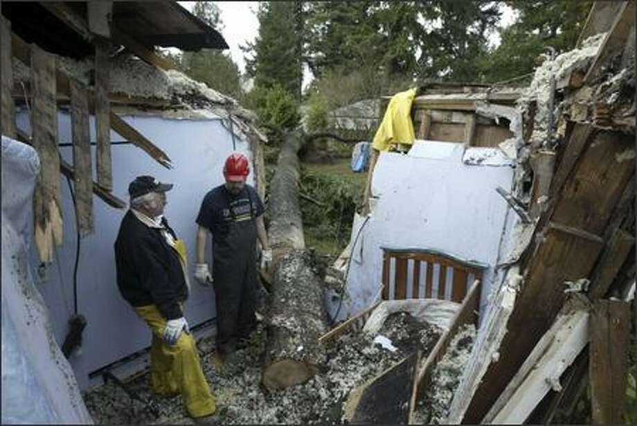 Galen Looney, left, and Sean Hill, with the disaster restoration company Belfor, survey the damage after a 120-foot tall tree fell in the Lake City area, ripping through a nursery in which 2 children slept just moments before. A one-year-old baby was removed from her crib and the room about five minutes prior to the tree falling around 1:00 a.m. Friday, Dec. 15, 2006. A second child, sleeping in a small bed that was partially crushed by the tree, received only scrapes. Photo: Andy Rogers, Seattle Post-Intelligencer