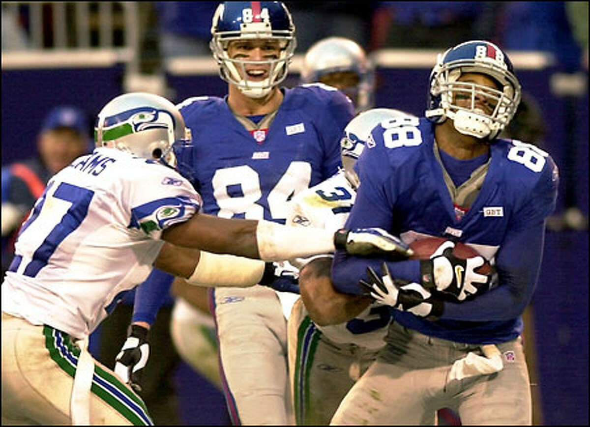 Giants receiver Ike Hilliard cradles the ball for the winning TD in front of teammate Joe Jurevicius as Seahawks cornerback Willie Williams, left, and safety Marcus Robertson try to defend.