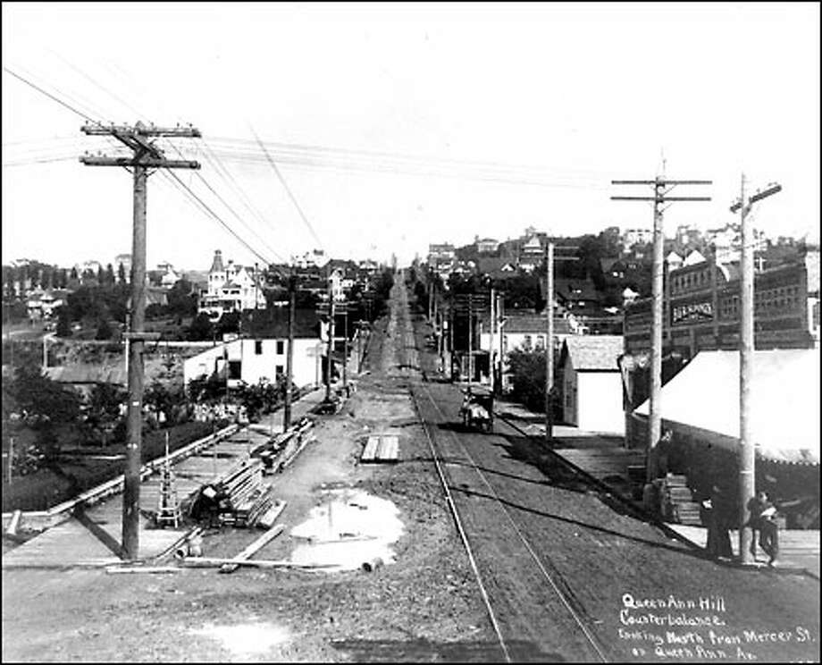Queen Anne Counterbalance, 1902: Looking north from Mercer Street, trolley tracks run up the face of Queen Anne Hill. The earliest trolleys that climbed the hill were aided by a counterweight that traveled in a tunnel under the street. Buses replaced trolleys in 1940. Photo: Seattle Post-Intelligencer