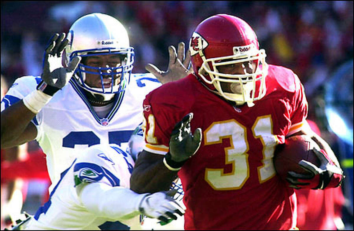 Kansas City's Priest Holmes ran for 120 yards on 26 workmanlike carries, with no run longer than 12 yards. Seattle's Reggie Tongue, back, and Shawn Springs pursue on this play.