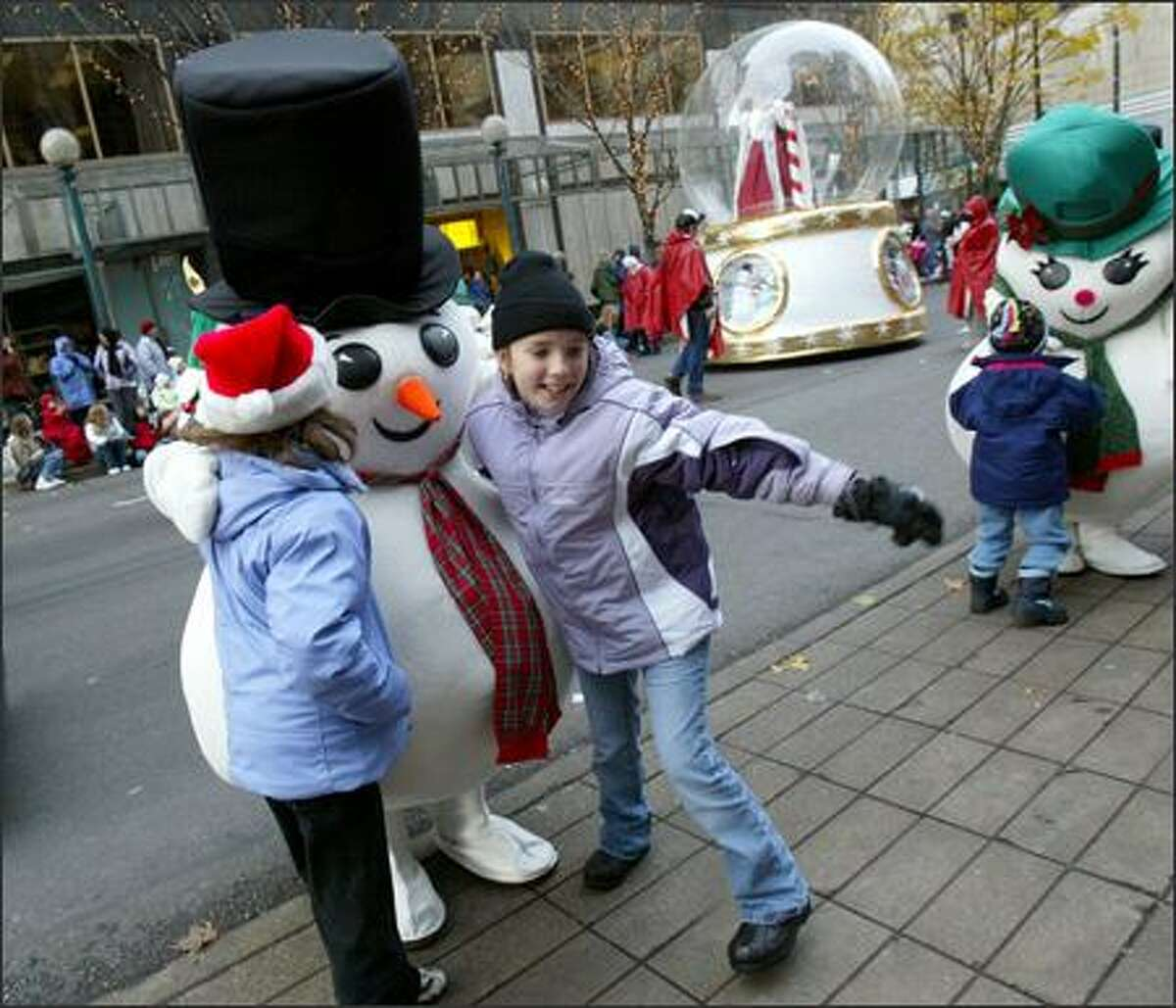 Sydney Horton, 9, (right) from Renton, and Kaylie Bentler, 9, from Des Moines, have their photo taken with one of the snowmen from Macy's during Macy's Holiday Parade in downtown Seattle on Friday.