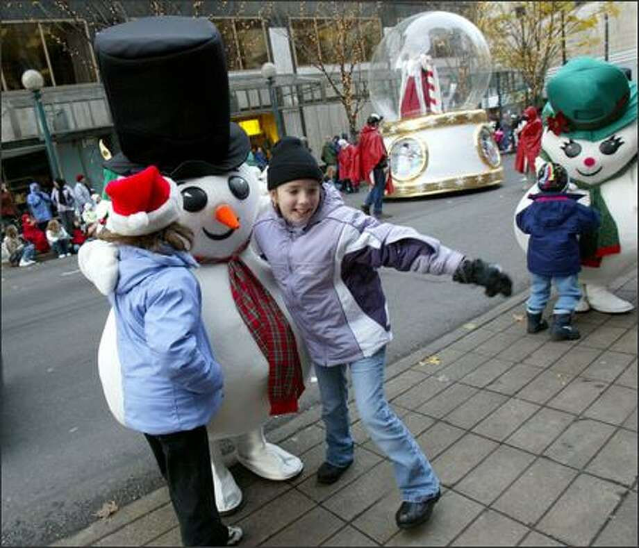 Sydney Horton, 9, (right) from Renton, and Kaylie Bentler, 9, from Des Moines, have their photo taken with one of the snowmen from Macy's during Macy's Holiday Parade in downtown Seattle on Friday. Photo: Karen Ducey, Seattle Post-Intelligencer