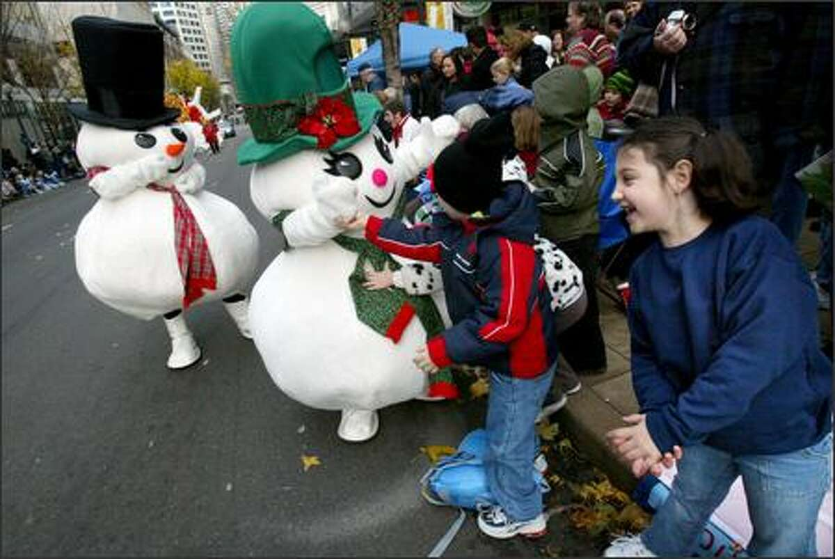Makayla Shipley, 6, (right) from Lynnwood, can't wait to hug one of the Macy's snowmen during the Macy's Holiday Parade in downtown Seattle on Friday.