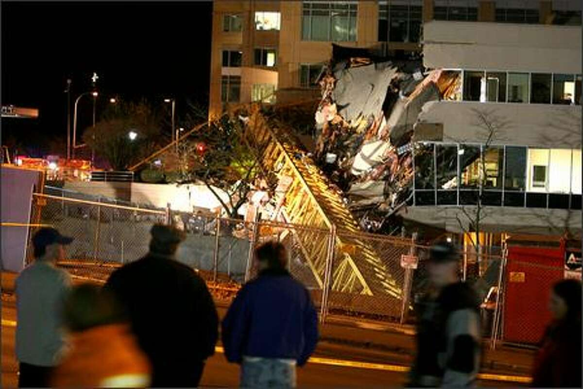 Onlookers look at the destruction from the crane that fell and hit at least three buildings in downtown Bellevue Thursday night.