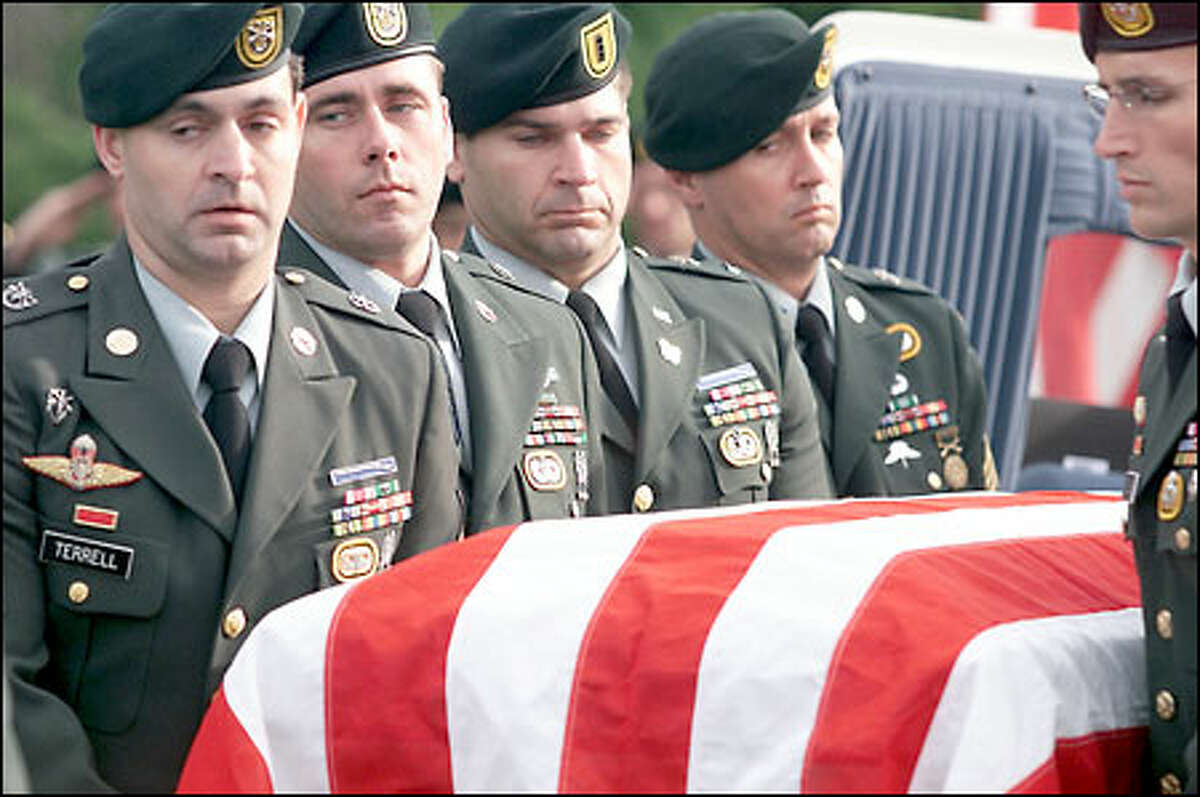 Members of the U.S. Army Special Forces carry Sgt. 1st Class Nathan Chapman's casket to his final resting place at Tahoma National Cemetery in Kent. Chapman, the first U.S. soldier killed by enemy fire in Afghanistan, was a member of the 1st Special Forces Group based at Fort Lewis.