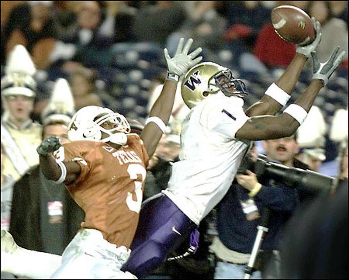 Washington wide receiver Reggie Williams gets a hand on a Cody Pickett pass with time running out in the second quarter, but was unable to hold on. Texas' Nathan Vasher defends.