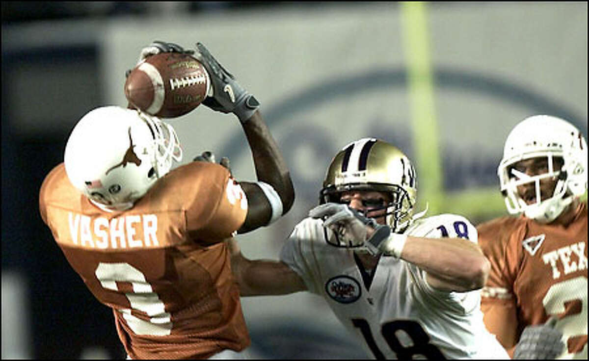 Washington's Todd Elstrom watches Texas Longhorns Nathan Vasher intercepts a Cody Pickett pass in the second quarter.